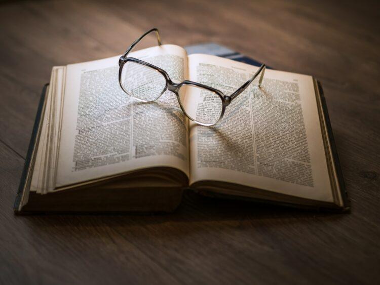 framed eyeglasses on top open book